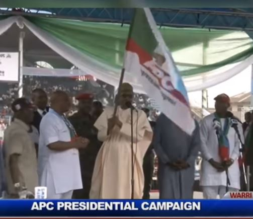 'I Hand Over This Flag To Our Governortorial Candidate' – Watch As Buhari Publicly Goofs Again In Warri